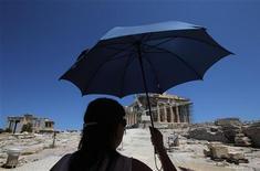Туристка смотрит на Парфенон на афинском Акрополе, 10 июля 2011 года. Новая и более значительная реструктуризация греческого долга вероятна в следующие два года, заявил представитель рейтингового агентства Standard & Poor's, добавив, что дальнейшее понижение суверенного рейтинга страны практически неизбежно. REUTERS/John Kolesidis