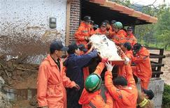 Спасатели выносят из дома тело погибшего в результате оползня в городе Чхунчхон, 27 июля 2011 года. Вызванный проливными дождями оползень сошел на южнокорейский горный курорт рано утром в среду, став причиной гибели по меньшей мере 13 человек, сообщили власти. REUTERS/Jo Yong-Hak