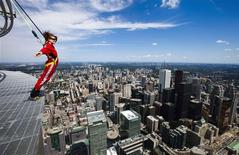 "<p>A reporter leans over the edge of the catwalk during the media preview for the ""EdgeWalk"" on the CN Tower in Toronto, July 27, 2011. REUTERS/Mark Blinch</p>"