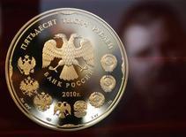 Коллекционная монета на заводе в Санкт-Петербурге, 9 февраля 2010 года.Рубль снизился утром четверга к доллару США, дорожающему против евро на фоне обострения европейских долговых проблем, и лишь минимально ослабел к бивалютной корзине, несмотря на тенденции бегства от риска, благодаря поддержке высоких цен на нефть и из-за возможных продаж валютной выручки под конец налогового периода. REUTERS/Alexander Demianchuk