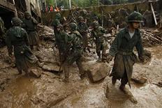 Солдаты убирают грязь после схода оползней в Сеуле, 28 июля 2011 года. Как минимум 53 человека погибли в Сеуле и его окрестностях в результате схода оползней, вызванных сильнейшими за последнее столетие ливнями в этом регионе. REUTERS/Truth Leem