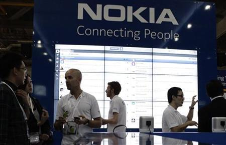 Staff members speak to trade visitors at the Nokia booth at the CommunicAsia expo in Singapore June 21, 2011. REUTERS/Tim Chong
