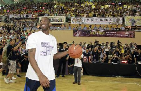 NBA basketball player Kobe Bryant of the Los Angeles Lakers smiles to fans upon his arrival at a stadium during his 2011 China Tour in Changsha, Hunan province July 16, 2011. REUTERS/Joe Tan/Files