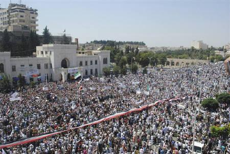 A giant Syrian flag is held by the crowd during a protest against President Bashar al-Assad after Friday prayers in the city centre of Hama July 29, 2011. REUTERS/Handout