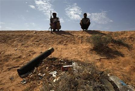 Libyan rebel fighters sit on a ridge near a tank shell after overrunning a government army position in the village of Hawamid in western Libya, July 30, 2011. REUTERS/Bob Strong
