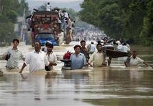 Residents carry their belongings through a flooded road in Risalpur, located in Nowshera District, in Pakistan's Northwest Frontier Province July 30, 2010.  REUTERS/Adrees Latif