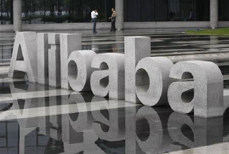 Two men chat beside a logo of Alibaba (China) Technology Co. Ltd at its headquarters on the outskirts of Hangzhou, Zhejiang province May 17, 2010. REUTERS/Steven Shi/Files