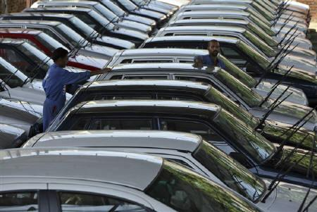 Workers clean parked cars at the Maruti Suzuki's stockyard on the outskirts of Jammu September 9, 2010. REUTERS/Mukesh Gupta/Files