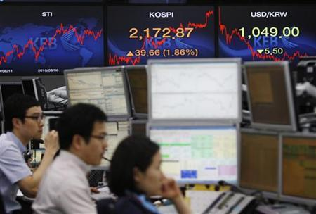 Currency dealers work at a dealing room as screens display the stock price index (top, 2nd R) and exchange rate between the Korean won and U.S. dollar (top R) at a bank in Seoul August 1, 2011. REUTERS/Truth Leem
