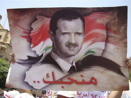 A government loyalists holds up a picture of Syria's President Bashar al-Assad during a protest outside the U.S. embassy in Damascus July 11, 2011.  REUTERS/Stringer/Files
