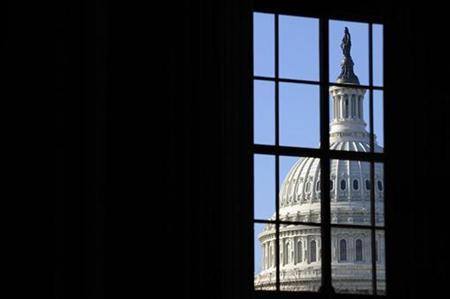 The dome of the US Capitol, where President Barack Obama will deliver his first address to a joint session of congress, is visible through a window on Capitol Hill in Washington, February 24, 2009. REUTERS/Jonathan Ernst