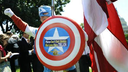 A man dressed as Captain America poses as dozens of Tea Party supporters rally near the U.S. Capitol against raising the debt limit in Washington, July 27, 2011. REUTERS/Jonathan Ernst