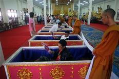 Буддийские монахи стоят позади гробов, куда ложаться посетители храма Прам-Мани, 28 мая 2011 года. Для тех, кого постигают неудача за неудачей, и у кого появилось желание начать жизнь заново один из тайских храмов предлагает нестандартное решение - репетицию смерти с имитацией похорон. REUTERS/Damir Sagolj