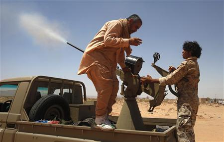 A young Libyan rebel test fires an anti-aircraft gun at a front line checkpoint near Tiji in western Libya, August 1, 2011. REUTERS/Bob Strong