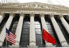 Флаги США (слева) и Китая на здании фондовой биржи на Уолл-стрит в Нью-Йорке, 30 марта 2011 года.  Глава центрального банка крупнейшего кредитора США - Китая - в среду призвал Вашингтон ответственно подойти к разрешению долгового кризиса, отметив, что скачки на рынке американских облигаций подорвут международную монетарную систему и помешают росту мировой экономики. REUTERS/Lucas Jackson