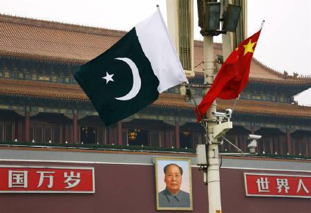 A Pakistan national flag flies alongside a Chinese national flag in front of the portrait of Chairman Mao Zedong on Beijing's Tiananmen Square during Pakistan' Prime Minister Yusuf Raza Gilani's visit May 18, 2011.         REUTERS/David Gray/Files