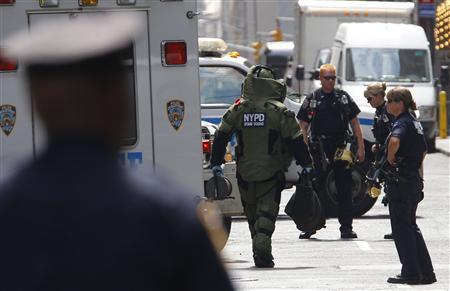 A New York City Bomb Squad officer wearing a protective suit walks to investigate a suspicious package on West 43rd Street in Times Square in New York, August 3, 2011. The package was found to be not a threat. REUTERS/Mike Segar