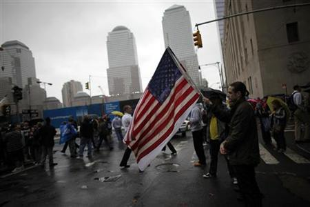 A man holds a U.S. flag while others pause for a moment of silence to pay their respects at the site of the former Twin Towers on the eighth anniversary of the 9/11 attacks on the World Trade Center in New York September 11, 2009. REUTERS/Carlos Barria