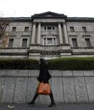 Женщина проходит мимо здания Банка Японии в Токио 21 декабря 2010 года. Банк Японии в четверг смягчил денежно-кредитную политику, расширив схему выкупа активов на заседании, которое было сокращено на один день в связи с интервенцией Токио на валютный рынок. REUTERS/Toru Hanai