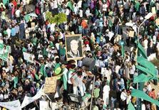 Сторонники ливийского лидера Муаммара Каддафи во время демонстрации в Эз-Завие 16 июля 2011 года. Лагерь Муаммара Каддафи ведет переговоры с исламистами, чтобы те повернулись против либералов, сказал сын ливийского лидера в интервью, что может быть попыткой посеять разногласия среди повстанцев после смерти одного из командующих военными силами.    REUTERS/Louafi Larbi