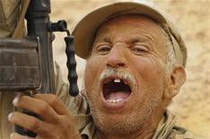 Ливийский повстанец кричит во время песочной бури в поселке на западе Ливии, 31 июля 2011 года. Жертвами последних бомбардировок НАТО стали 32 человека, в том числе один из главных руководителей правительственных войск и сын Муаммара Каддафи Хамис, заявил в пятницу представитель мятежников. REUTERS/Bob Strong