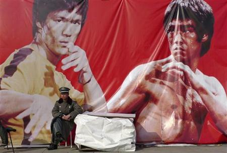 A security guard sits in front of an advertising poster of martial arts movie star Bruce Lee at the Olympic Park in Beijing November 4, 2009. Picture taken November 4, 2009. REUTERS/Stringer