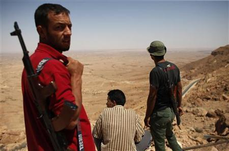 A group of Libyan rebel fighters look down onto the plains from an observation point in the Western Mountains near the town of Kabaw, August 2, 2011. REUTERS/Bob Strong