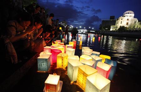 People pray after releasing paper lanterns on a river facing the gutted Atomic Bomb Dome in remembrance of atomic bomb victims on the 66th anniversary of the bombing in Hiroshima August 6, 2011. REUTERS/Kim Kyung-Hoon