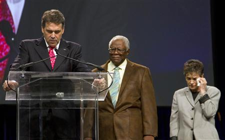 Texas Governor Rick Perry (L) prays with Reverend C. L. Jackson and Alice Patterson during ''The Response'', an event billed as a call to prayer for a nation in crisis, at Reliant stadium in Houston August 6, 2011. REUTERS/Richard Carson