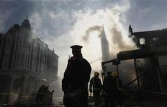 Пожарные тушат огонь в зданиях, подожженных во время погромов в лондонском районе Тоттенхэм, 7 августа 2011 года. Беспорядки продолжились в британской столице в ночь на понедельник, перекинувшись на район Энфилд. REUTERS/Luke MacGregor