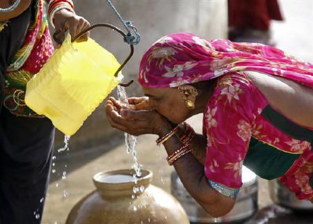 A woman drinks water as she waits for her turn to draw water from a well near the banks of the dried-up Dharji lake at Dharji village, west of Ahmedabad, May 14, 2011.  REUTERS/Amit Dave/Files
