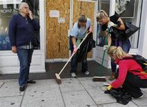 Moradores limpam rua na terça-feira após mais uma noite de violência em Londres.   REUTERS/Olivia Harris