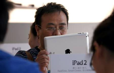 A customer looks at an iPad 2 during the China launch at an Apple Store in central Beijing May 6, 2011. REUTERS/David Gray/Files