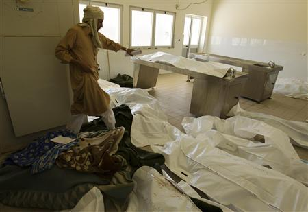 EDITOR'S NOTE: PICTURE TAKEN ON A GUIDED GOVERNMENT TOUR A morgue official walks over body bags containing the remains of those whom Libyan officials say were killed in houses bombed by NATO forces in Majar, a village south of Zlitan, east of Tripoli, August 9, 2011. REUTERS/Caren Firouz