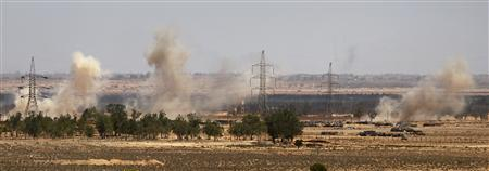 Smoke rises as Gaddafi government forces fire Grad missiles at Libyan rebel fighter positions in the town of Bir al-Ghanam in western Libya, August 10, 2011. REUTERS/Bob Strong