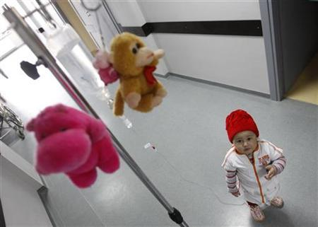 Mari, a 3 year-old leukaemia patient, stands next to her IV drip at the corridor of the onco-hematology department of the Iashvili Central Children's Hospital in Tbilisi April 7, 2011. REUTERS/David Mdzinarishvili