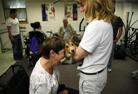 Multiple sclerosis patient Sue Sutton (L) embraces Dare, a two-legged Sheltie dog used in therapy for disabled people in Denver, Colorado July 15, 2009. REUTERS/Rick Wilking