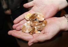 Работник Монетного двора США держит новые монеты номиналом $1 во время церемонии, посвященной началу их обращения, Нью-Йорк, 15 февраля 2007 года. Резкий скачок цен на золото заставил Монетный двор США приостановить во вторник онлайн-продажи золотых коллекционных монет впервые за долгие годы, сообщил его представитель. REUTERS/Brendan McDermid