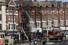 Пожарные тушат огонь в районе Клэпхэм на юге Лондона, 9 августа 2011 года. Британские власти подумают о применении военной силы в случае новых погромов, сказал в четверг Дэвид Кэмерон, пытающийся обуздать ставший испытанием для его премьерства кризис. REUTERS/Stefan Wermuth