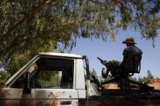 A Libyan rebel fighter mans an anti-aircraft gun at a front line position in the town of Bir al-Ghanam in western Libya, August 9, 2011.  REUTERS/Bob Strong