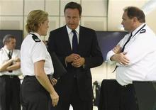 Primeiro-ministro britânico, David Cameron, conversa com policiais em Birmingham, na região central da Inglaterra. 10/08/2011 REUTERS/Jeff J Mitchell/pool
