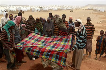 Recently arrived refugees from Somalia bury the body of 18-month-old Sahro Mohamed, who died of acute severe malnutrition and dehydration, at the Kobe refugee camp, near the Ethiopia-Somalia border, August 12, 2011. REUTERS/Thomas Mukoya