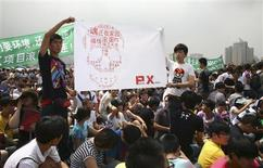 "Residents hold a banner with Chinese characters forming a shape of a skull which reads ""Get out PX (paraxylene), give us back our home, never give up"" as they demonstrate against a petrochemical plant at the People's Square in Dalian, Liaoning province August 14, 2011.REUTERS/Stringer"