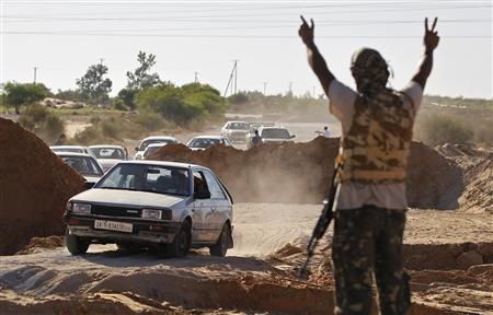 A rebel fighter raises his arms as a convoy of residents flee fighting between rebels and government forces loyal to Libya's leader Muammar Gaddafi near the coastal town of Zawiyah, 50 km (30 miles) west of Tripoli, August 14, 2011. REUTERS/Bob Strong