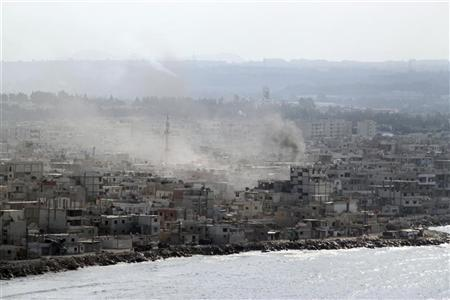 Smoke rises in the city of Latakia August 14, 2011. REUTERS/Handout