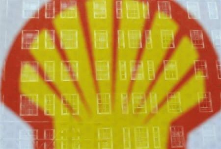 Apartment windows are seen behind a logo at a Shell petrol station in central London July 29, 2010. REUTERS/Toby Melville/Files