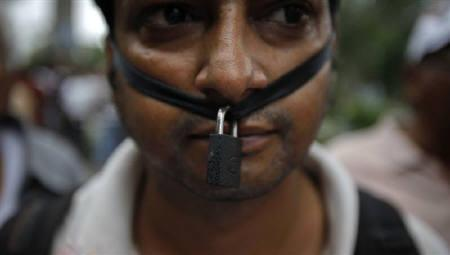 A supporter of veteran Indian social activist Anna Hazare wears a symbolic lock around his mouth while taking part in an anti-government rally against corruption in New Delhi August 16, 2011. REUTERS/Adnan Abidi