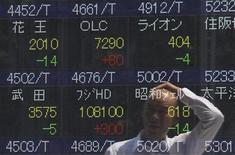 Мужчина отражается в электронном табло Токийской фондовой биржи 11 августа 2011 года. Фондовые рынки Азии закрылись в среду снижением, так как совместное заявление лидеров Германии и Франции не смогло убедить инвесторов в способности властей еврозоны усмирить долговой кризис. REUTERS/Yuriko Nakao
