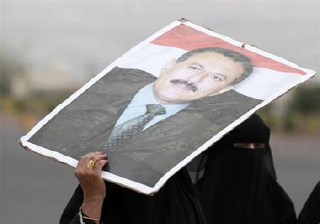 Supporters of Yemen's President Ali Abdullah Saleh holds his picture ahead of Friday prayers in Sanaa, Yemen August 12, 2011. REUTERS/Jumana El Heloueh