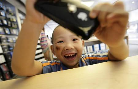 A 5-year-old boy plays games on an iPhone in the company's flagship store in Beijing's Sanlitun Area, July 22, 2011. China Mobile Ltd, the world's biggest mobile operator, has met with Apple Inc Chief Executive Steve Jobs several times on introducing an iPhone based on its network standard. REUTERS/Jason Lee/Files